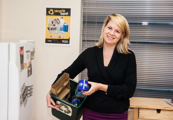 Young woman holding mixed recycling bin in kitchen © Zo Zhou